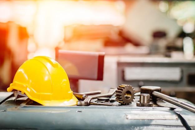 O capacete de segurança amarelo do capacete com instrumentos alinha ferramentas na fábrica para o fundo.