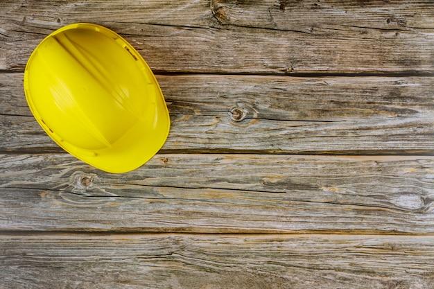 O capacete de segurança amarelo no canteiro de obras com mesa de madeira.
