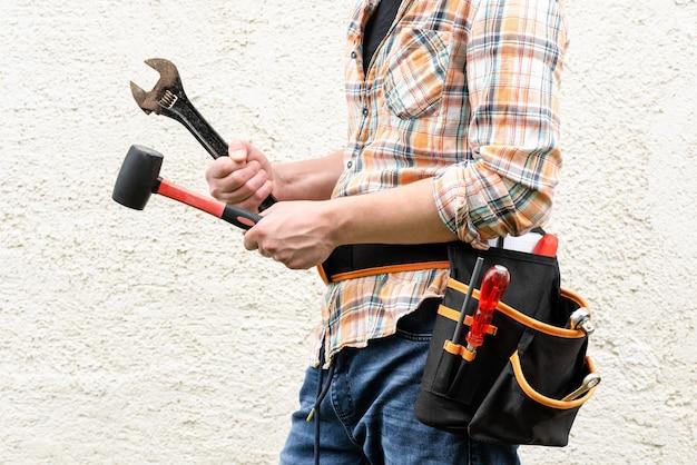 O capataz segura um martelo de borracha e uma chave ajustável nas mãos.