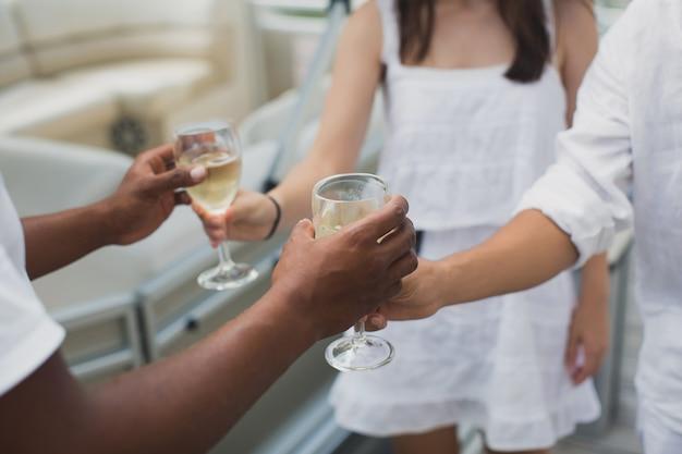 O capitão do iate presenteia seus convidados com uma taça de champanhe