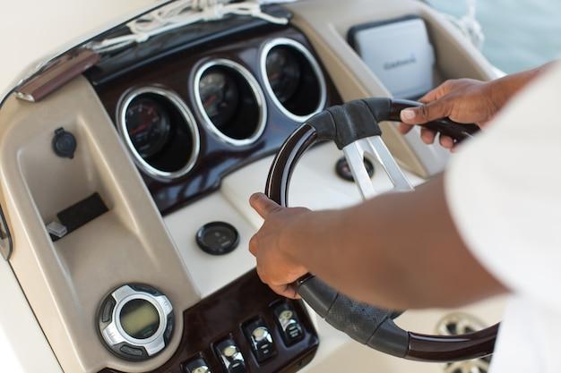 O capitão do iate segura o volante com as mãos