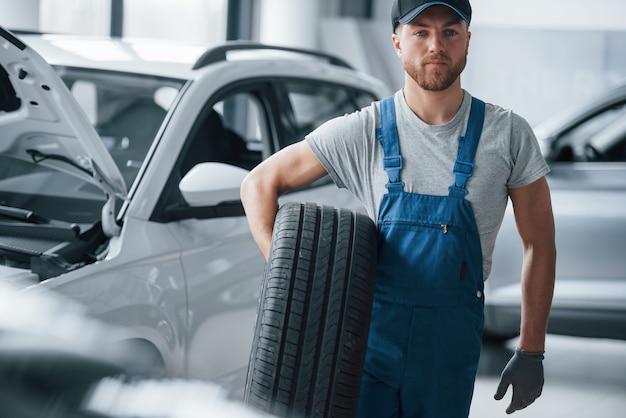 O capô está aberto no outro carro. mecânico segurando um pneu na oficina. substituição de pneus de inverno e verão.