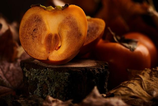 O caqui cortado fresco frutifica nas folhas de outono alaranjadas em um fundo de madeira.
