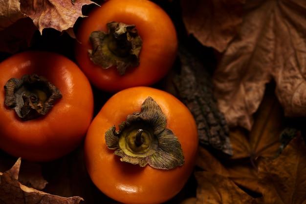 O caqui fresco frutifica nas folhas de outono alaranjadas em um fundo de madeira, vista superior.