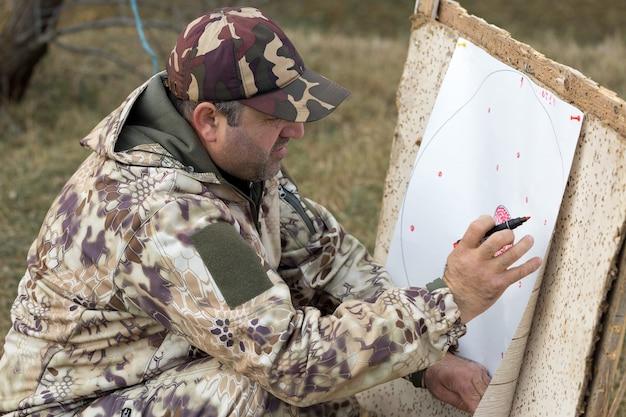 O cara anota os resultados dos tiros no alvo. um homem camuflado atira de cartuchos