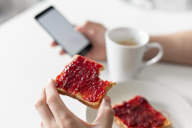 O cara assiste as notícias no telefone durante o café da manhã