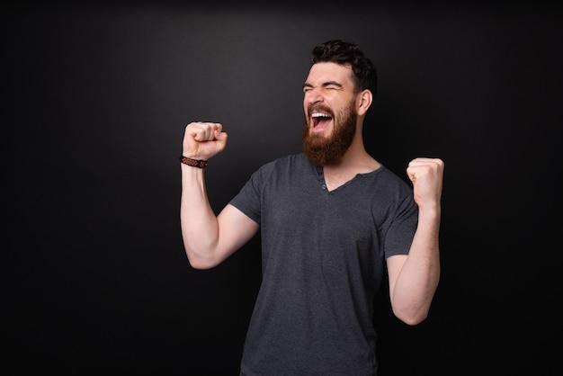 O cara barbudo bonito é o vencedor, gritando e comemorando com as mãos rosadas sobre um fundo escuro
