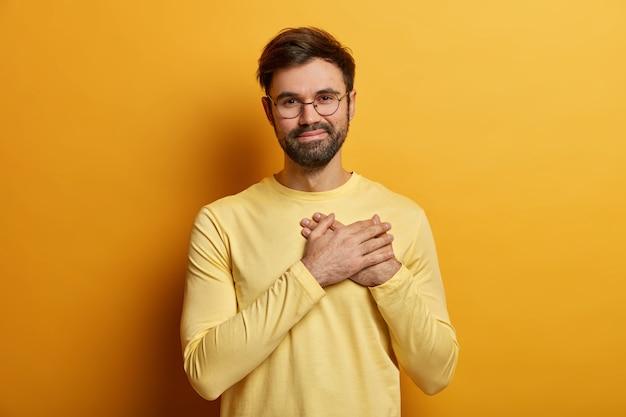 O cara barbudo bonito mantém as mãos no coração, expressa emoções sinceras, agradece a ajuda e palavras comoventes, fica grato, usa um macacão amarelo casual e posa dentro de casa. conceito de linguagem corporal