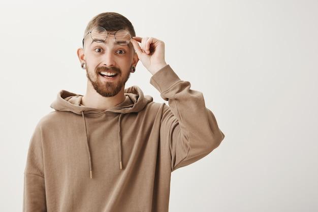 O cara barbudo bonito tira os óculos e parece animado, sorrindo feliz