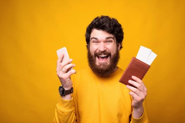 O cara barbudo está empolgado com a viagem, segurando nas mãos o passaporte com ingressos e telefone.