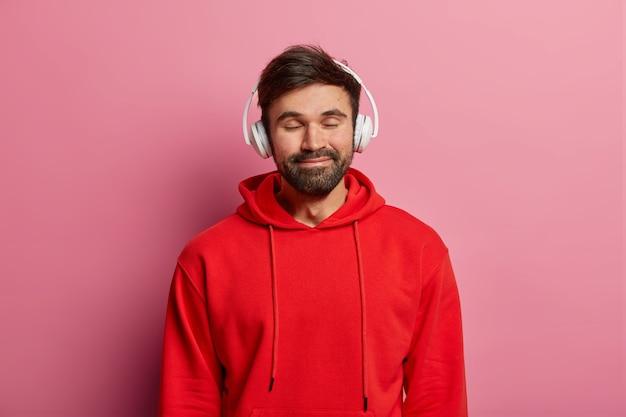 O cara barbudo satisfeito gosta de ouvir música em fones de ouvido estéreo, fecha os olhos e sorri gentilmente, usa um moletom vermelho, se sente bem, é modelo em uma parede rosa pastel. adolescentes, hobby, conceito de estilo de vida