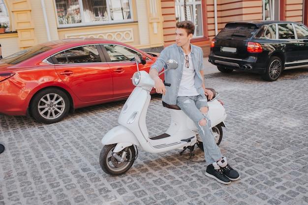 O cara bonito e bonito está sentado no banco da motocicleta e encostado nele