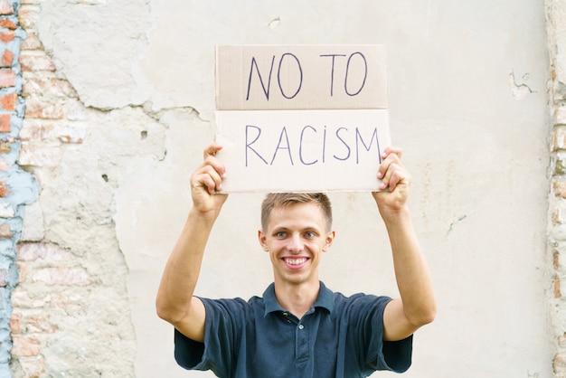 O cara caucasiano saiu para protestar contra o racismo com um pôster em suas mãos, jovem aparência ...