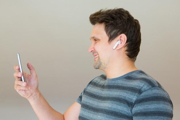 O cara coloca um fone de ouvido sem fio no ouvido e começa a falar ao telefone usando um link de vídeo
