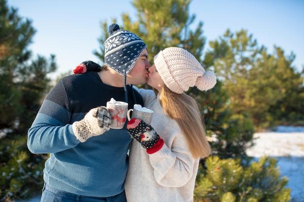 O cara com a garota anda e beija na floresta de inverno com uma caneca de bebida quente.