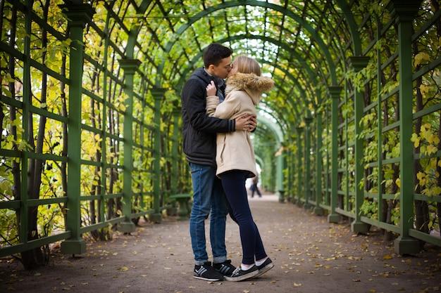 O cara com a garota carinhosa no parque.