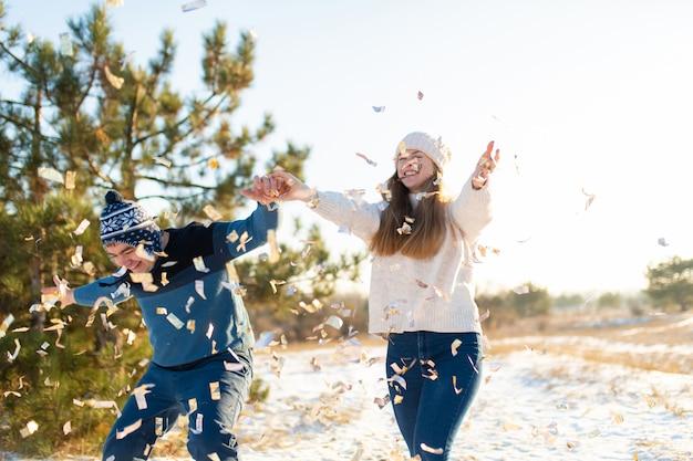 O cara com a garota joga confete na floresta de inverno
