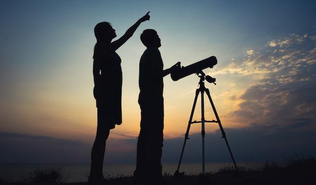 O cara com a garota olhando para o céu através de um telescópio