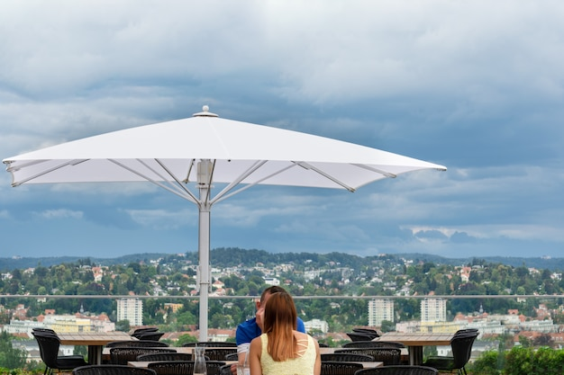 O cara com a menina está sentado em um café com uma bela vista da cidade de graz.