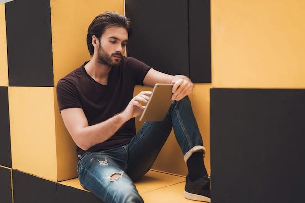 O cara com o tablet senta-se em mobiliário moderno.