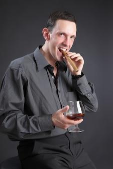 O cara com um charuto e conhaque em um fundo preto