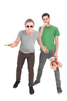 O cara com uma faca e o cara com um brinquedo infantil isolado em uma parede branca. o conceito do bem e do mal