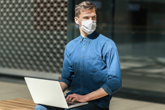 O cara da cidade com uma máscara protetora está trabalhando em um laptop