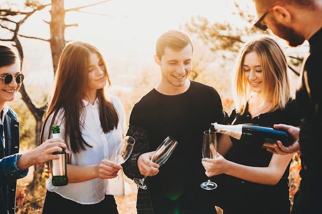 O cara da colheita servindo champanhe em taças de jovens amigos enquanto festeja na natureza em um dia ensolarado