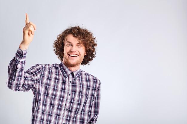 O cara de cabelo encaracolado levantou o cara feliz com a ideia com uma emoção positiva