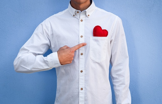 O cara de camisa branca aponta o dedo para um dia dos namorados vermelho em seu bolso