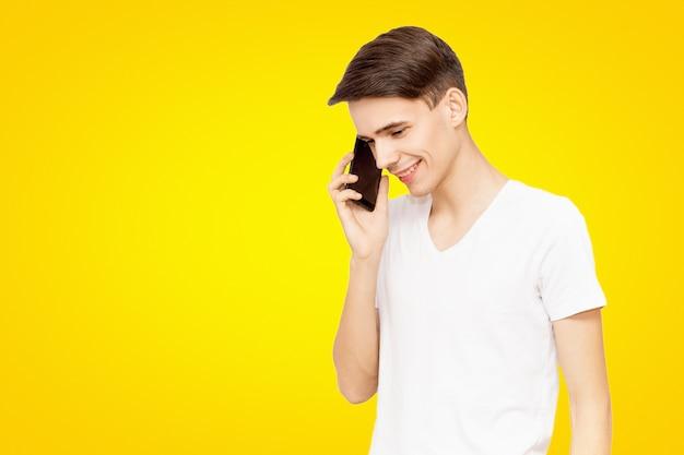O cara de camiseta branca, falando no telefone sobre um fundo amarelo isolado, falador jovem, alegre homem na vida