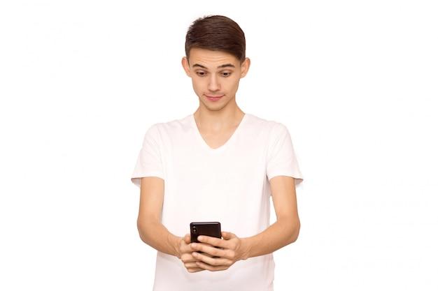 O cara de camiseta branca, olha para o telefone, isolado