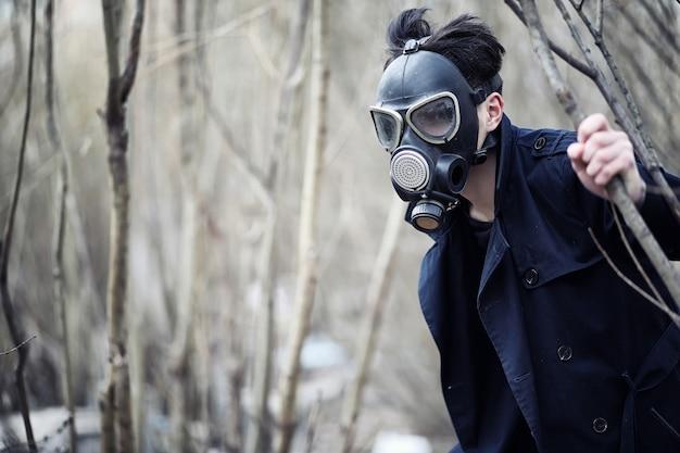 O cara de casaco e máscara de gás. retrato pós-apocalíptico asiático mascarado da radiação. o menino é coreano com uma máscara de envenenamento por gases. máscara pós-nuclear no asiático.