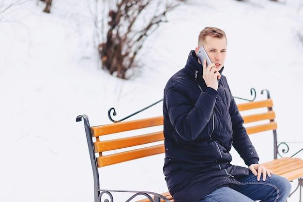 O cara de jaqueta de inverno fala ao telefone na rua