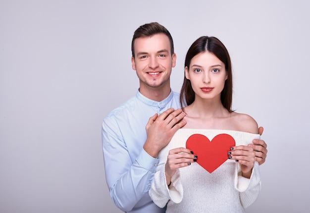 O cara de sorriso agradável abraça a mulher bonita que está holdingred o coração do cartão