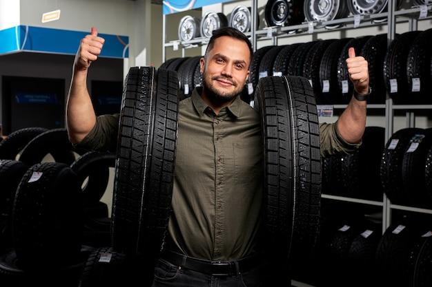 O cara do cliente fica com dois pneus por rack de pneus, ele fez a escolha, comprar os melhores na oficina mecânica, mostrando o polegar para cima na câmera, feliz. retrato