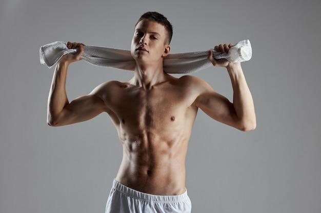O cara do esporte, segurando toalhas atrás da cabeça, levantou a imagem para a imprensa. foto de alta qualidade
