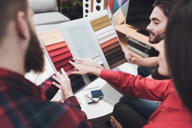 O cara e a garota escolhem as amostras de cores com o designer.