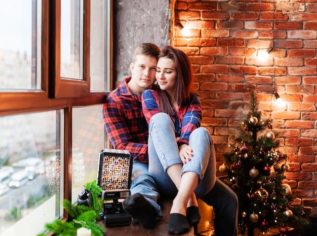 O cara e a garota estão se abraçando na janela. um casal apaixonado se alegra na véspera de ano novo. história de amor de ano novo