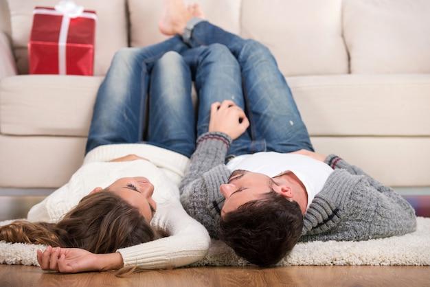 O cara e a menina estão deitados no chão com as pernas no sofá.