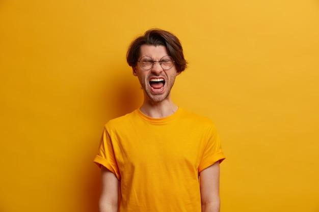 O cara emocional fica com a boca bem aberta, grita de decepção, grita com os olhos fechados, sente-se perturbado porque perdeu uma aposta enorme, vestido com uma camiseta amarela brilhante, perde a paciência, tem problemas de vida
