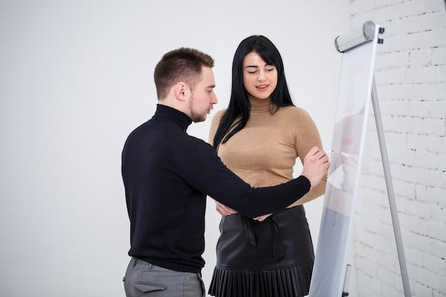 O cara empresário, professor, mentor ensina uma garota especialista, uma aluna. conceito de jornada de trabalho