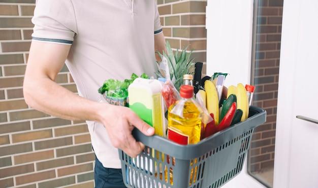 O cara entrega a cesta cheia de mantimentos na porta da casa. compras online.