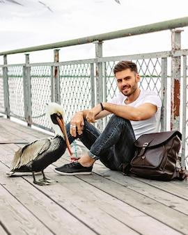 O cara está alimentando um pelican sentado no cais sorrindo
