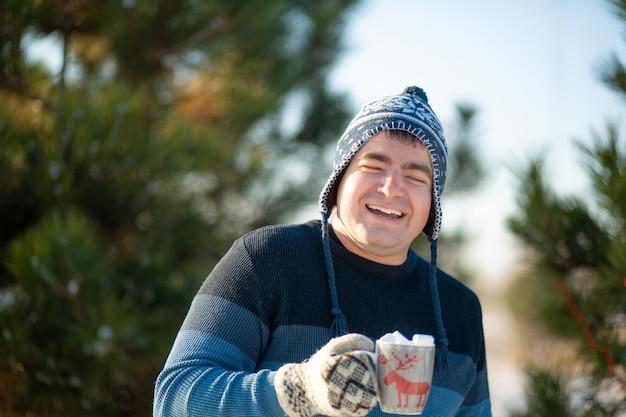 O cara está bebendo uma bebida quente com marshmallows no inverno na floresta.