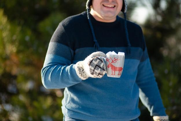 O cara está bebendo uma bebida quente com marshmallows no inverno na floresta