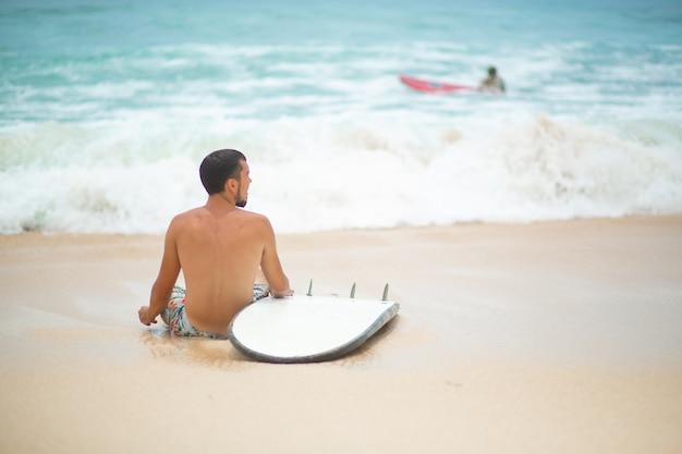 O cara está descansando em uma praia tropical, depois de surfar.