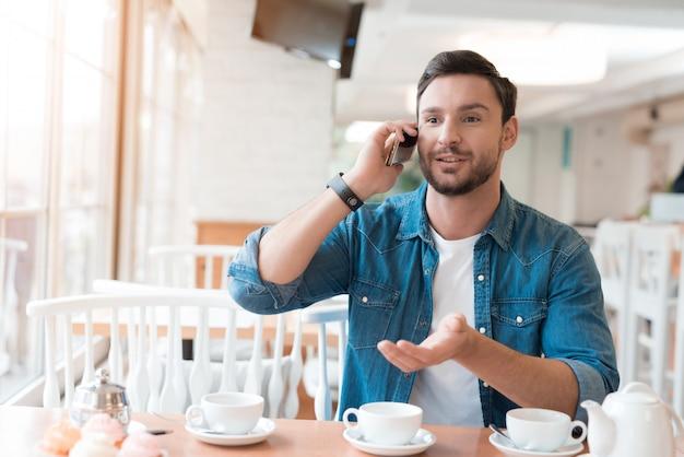 O cara está falando ao telefone em um café.