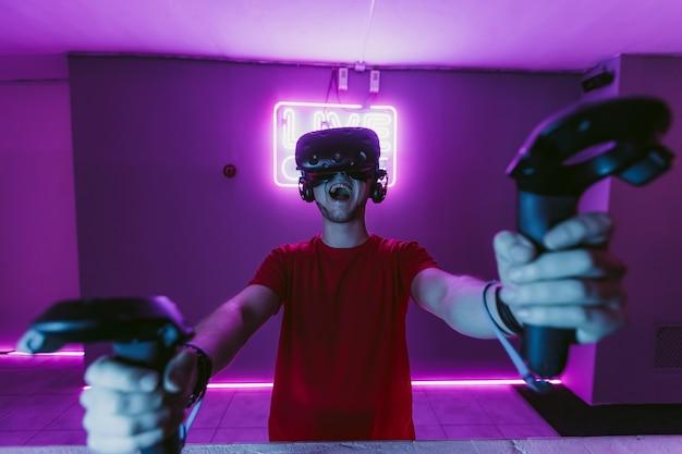 O cara está jogando um jogo de tiro online na sala de néon do jogo