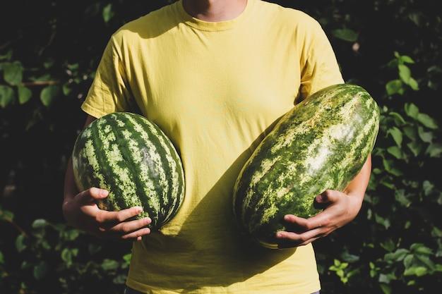 O cara está segurando melancias nas mãos